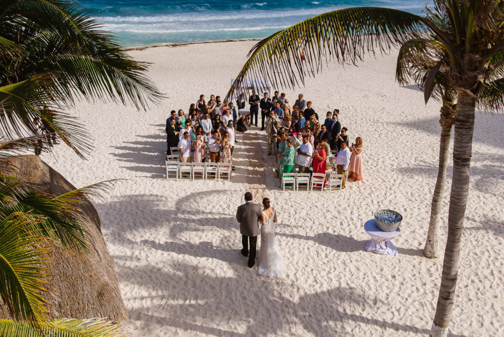 High shot bride and Father of the bride walking down the aisle at Panama Jack beach ceremony in Cancun with Palmtrees and beautiful caribbean sea