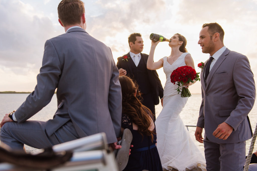 Bride drinking champagne from the bottle on a boat with bridal party and groom at sunset in Cancun