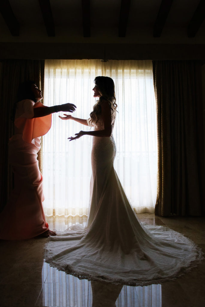 Mother of the bride reaches to hold her daughter infront of the window at Secrets Capri