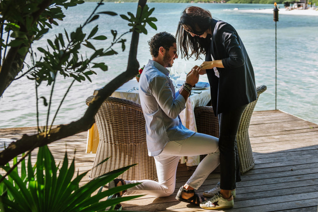 Wedding proposal, the soon to be groom on one knee outting the ring on the soon to be bride finger at Nizuc Resort dock