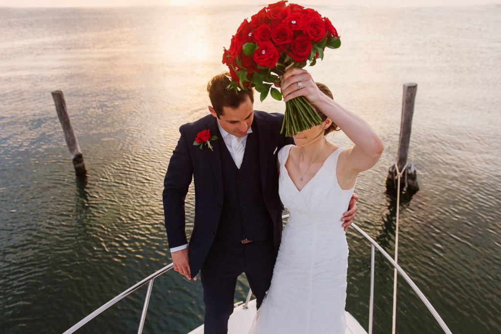 Bride and groom on a boat holding a red roses bouquet during lagoon sunset in Cancun