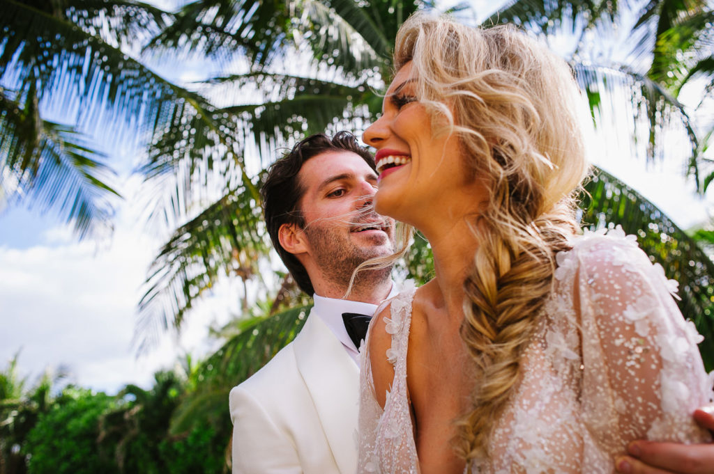 Close up of laughing bride while groom holds her for portraits at Viceroy Riviera Maya Wedding