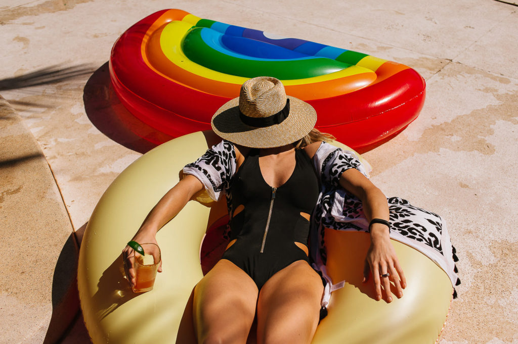 wedding guest sunbathing laying on an inflatable with a hat on her face.