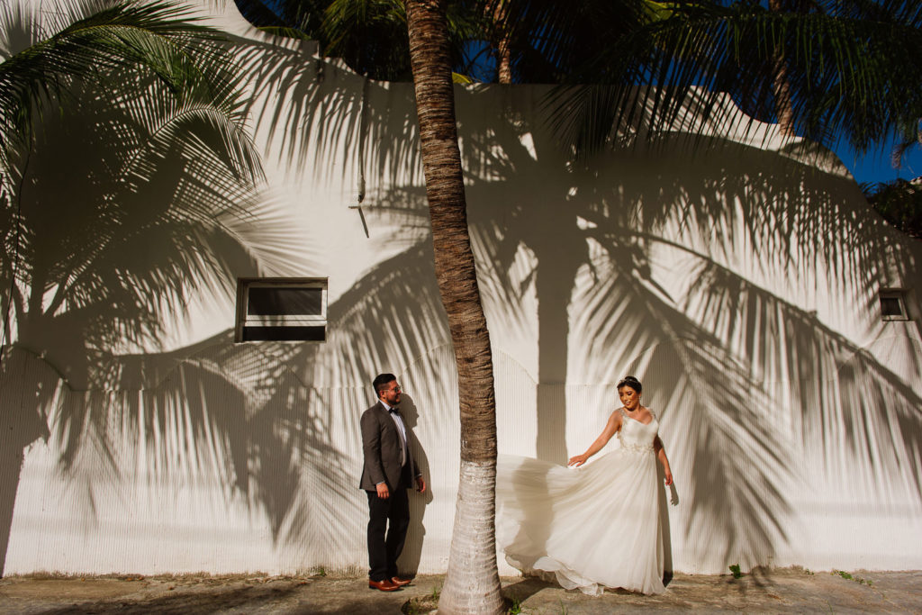 Palmtree shadows piano a white wall with bride and groom posing in Puerto Morelos