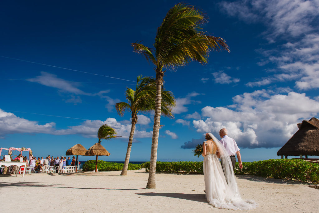 Bride and Father of the bride walking down the aisle to get to the beach gazebo with tree palm trees and blue sky at Hard Rock Riviera Maya