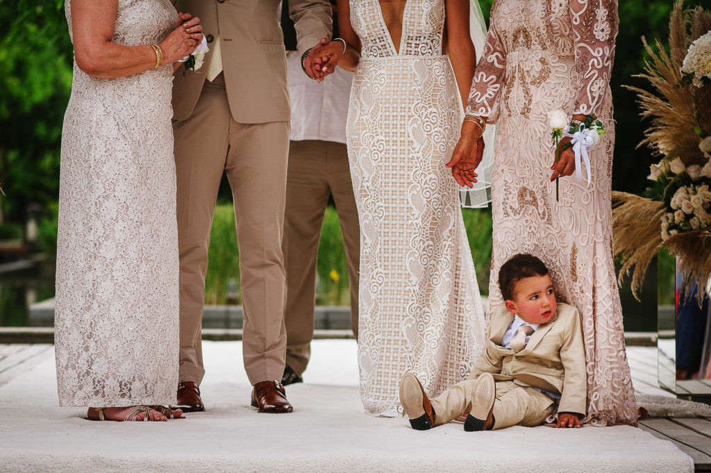 Funny ring bearer tired during ceremony sitting by his grandmother's feet during ceremony in Nizuc Cancun