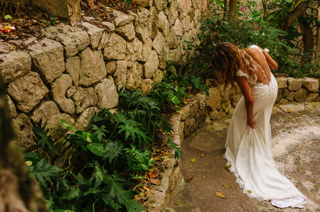 Bride holds the train of her wedding gown walking at Xcaret Park