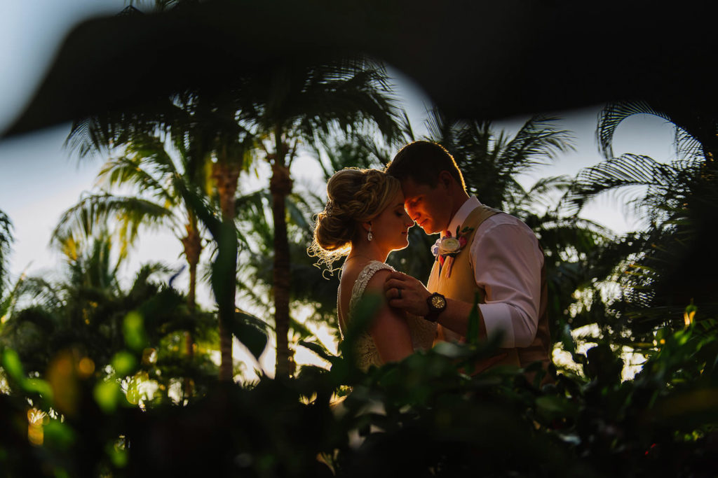 Bride and groom portrait with beautiful sunset light between jungle trees and palmares