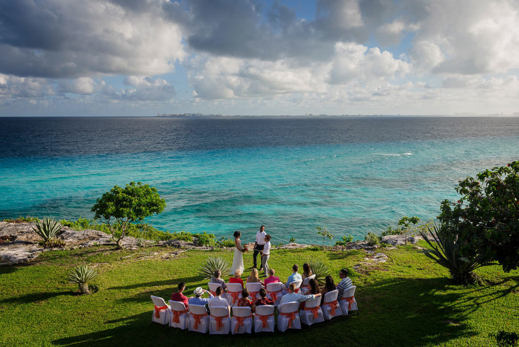 Arenal shot of ceremony by the cliff of Isla Mujeres overlooking the blue ocean and a green garden with chairs for the wedding guests LGBQT ceremony