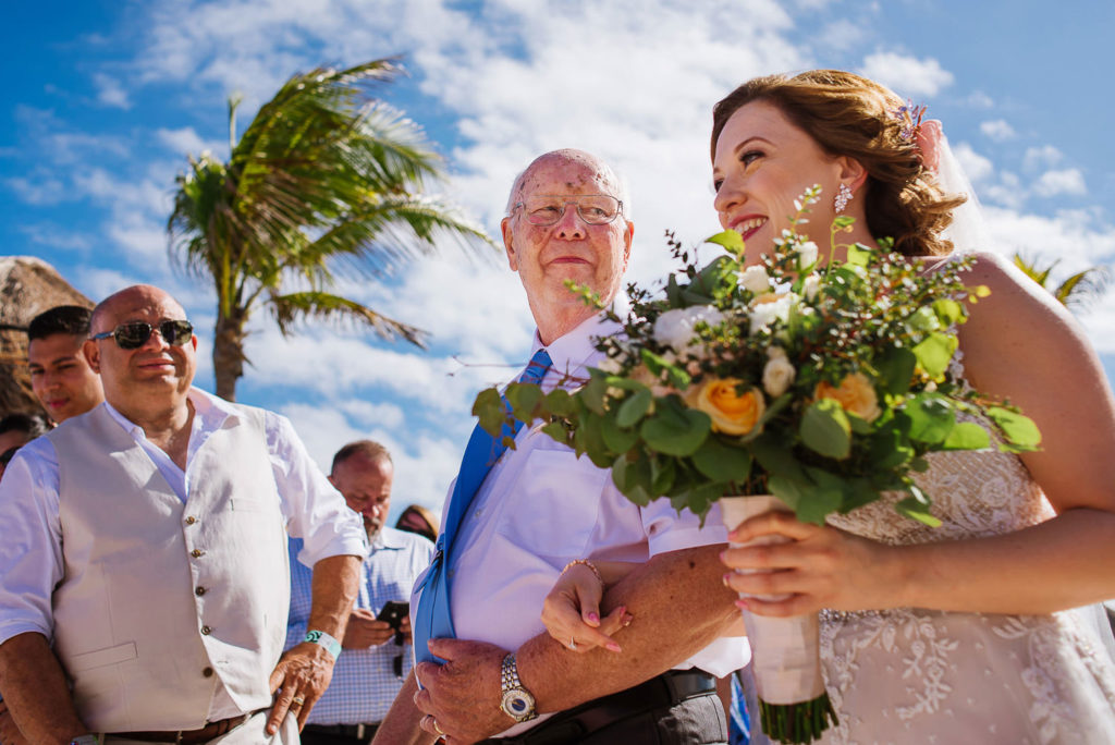 Father of the bride looks at the bride while he walks her down to aisle at a Riviera Maya Wedding