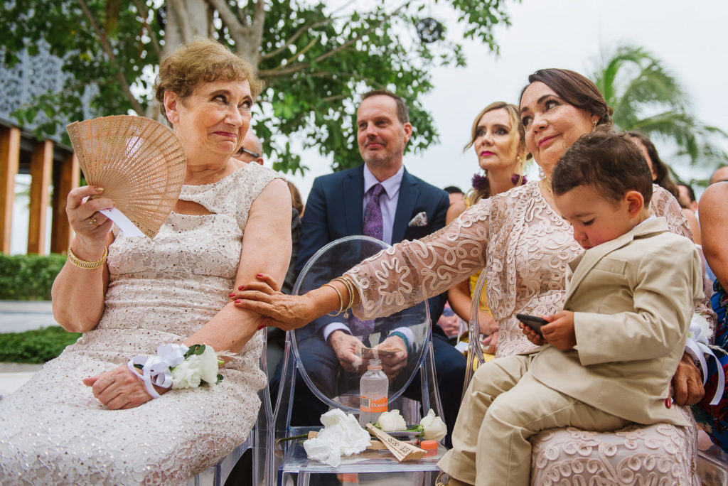 Mother of the bride and Mother of the groom exchange looks during ceremony with Grandson sitting on her lap in Nizuc Hotel & SPA
