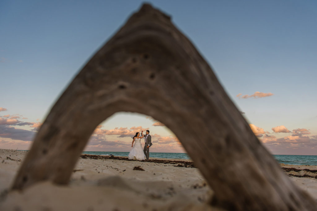 Isla Blanca portrait session bride and groom framed with a wooden log during sunset on the beach