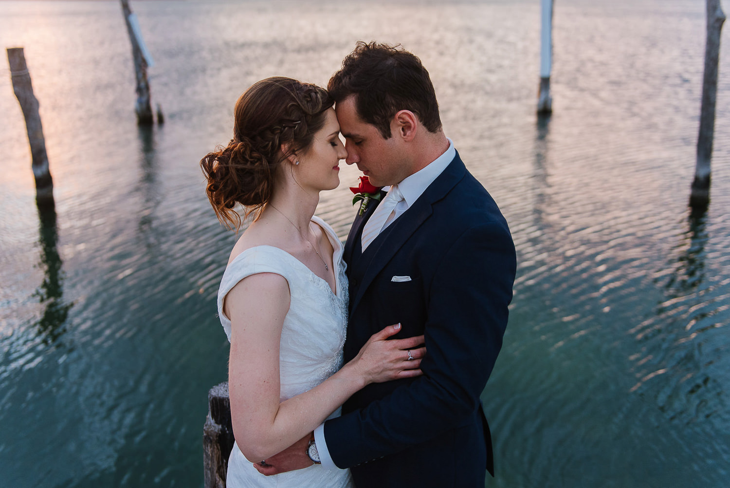 Bride and groom holding each other with a lagoon in the background