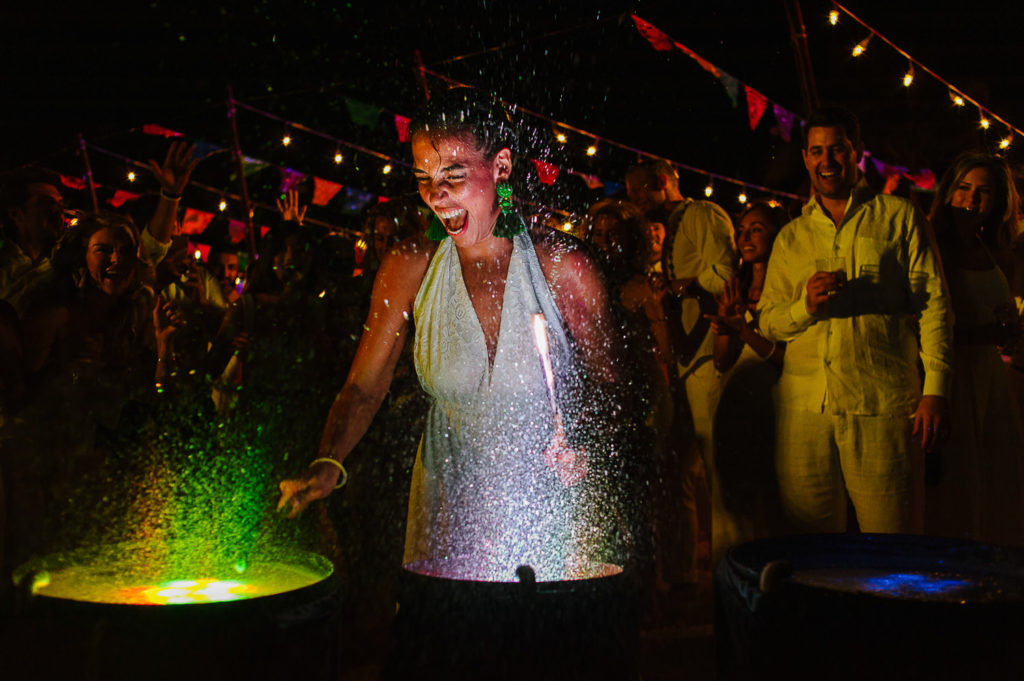 Colorful lit water drums wedding guest playing them at rehearsal dinner mexican party in Playa del Carmen
