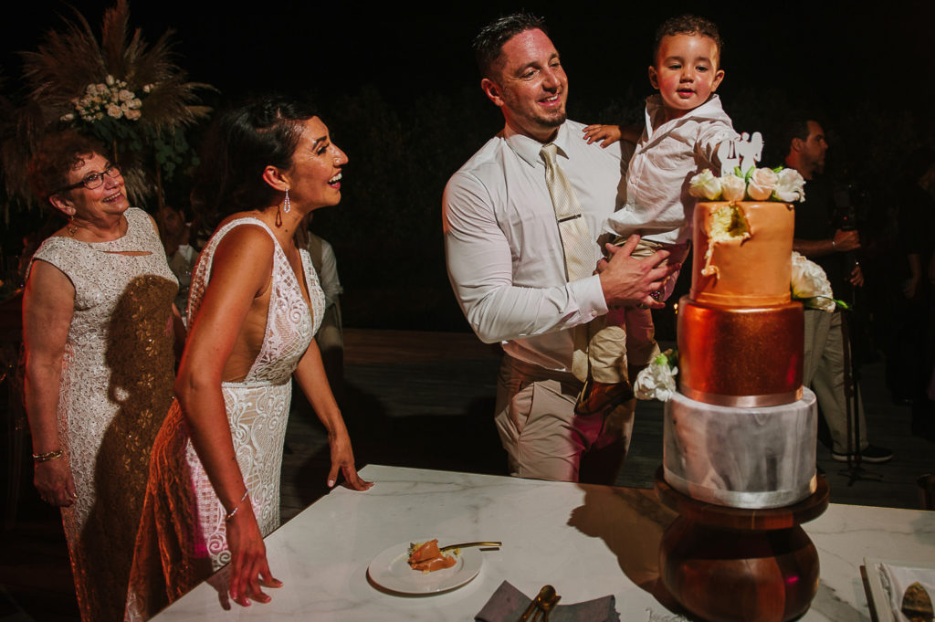 Wedding cake with awesome cake topper with bride, groom and son cutting it