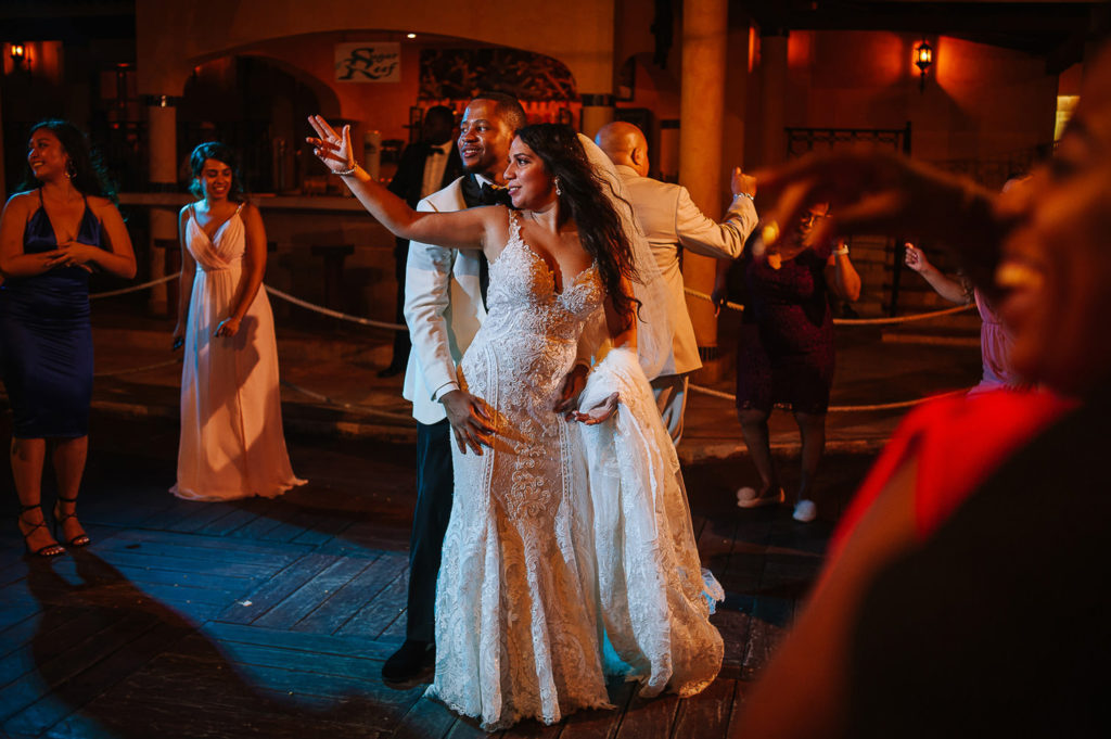 Bride and groom dancing during wedding reception with red lights outdoors party in Playa del Carmen