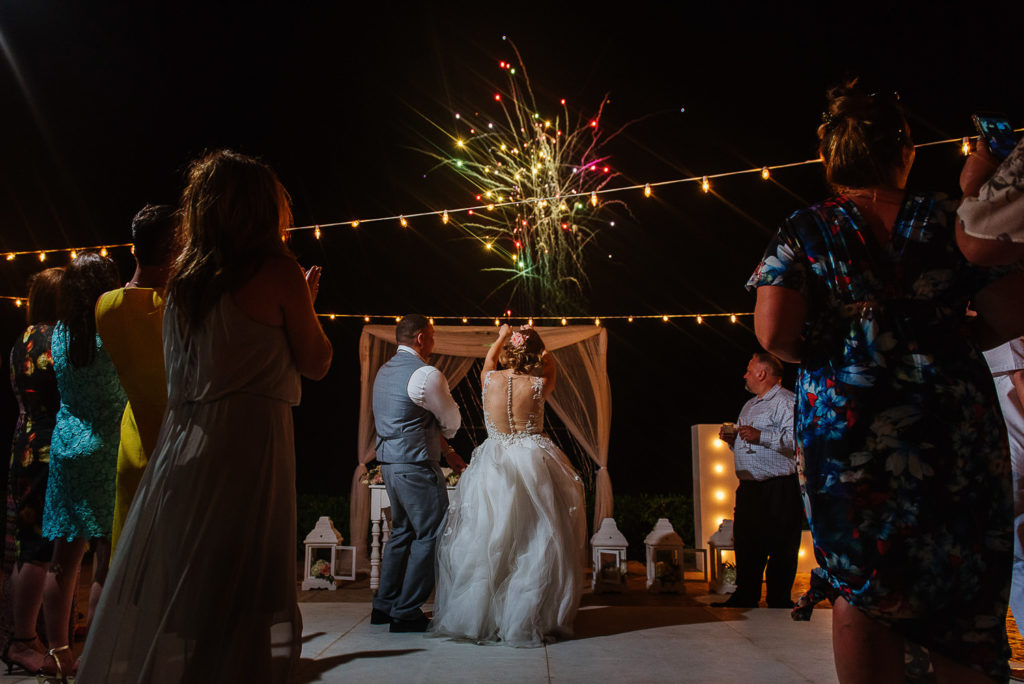Wedding guests and bride and groom enjoying fireworks in the sky at Hard Rock Riviera Maya wedding repcetion
