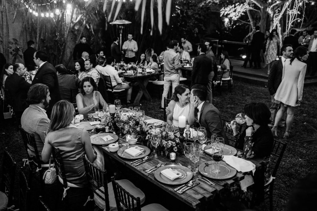 Outdoors garden intimate wedding reception in Cancun black and white bride and groom sitting at the table