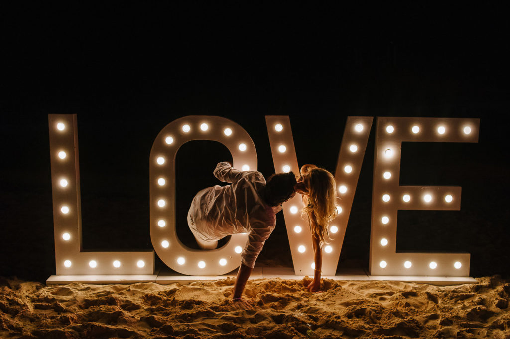 LOVE lightbulbs sign with bride and groom playing in it on the beach in Playa del Carmen
