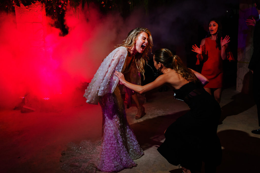 Laughing bride with red light on dance floor with friends at Viceroy Hotel in Playa del Carmen