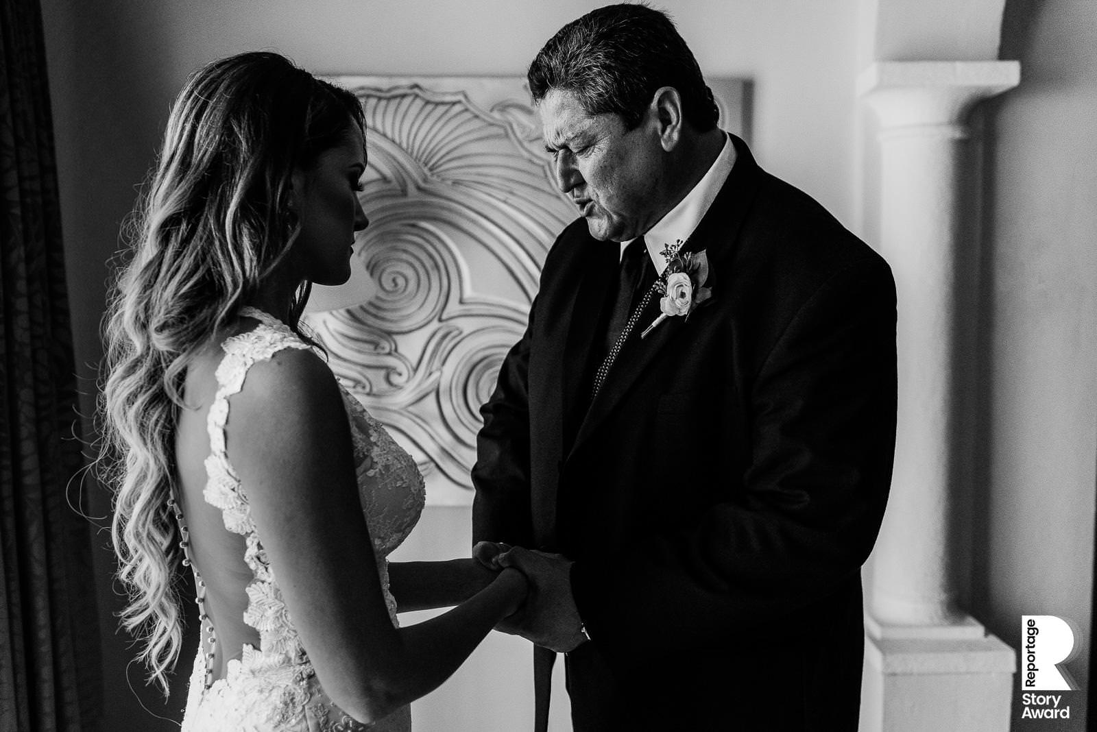 Black and white photo of the Father of the Bride giving her a catholic blessing and praying in Mexico