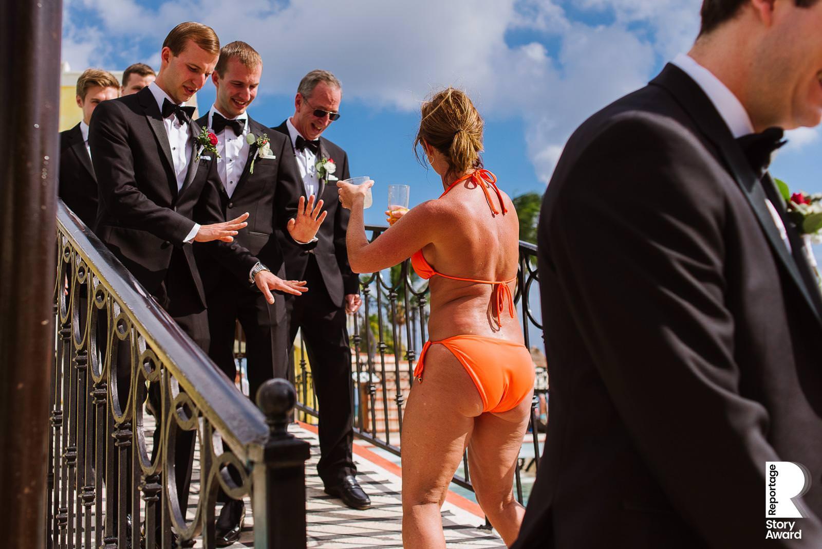 Tourist wearing an orange bikini offers a drink to a Groom wearing a tuxedo and he rejects it