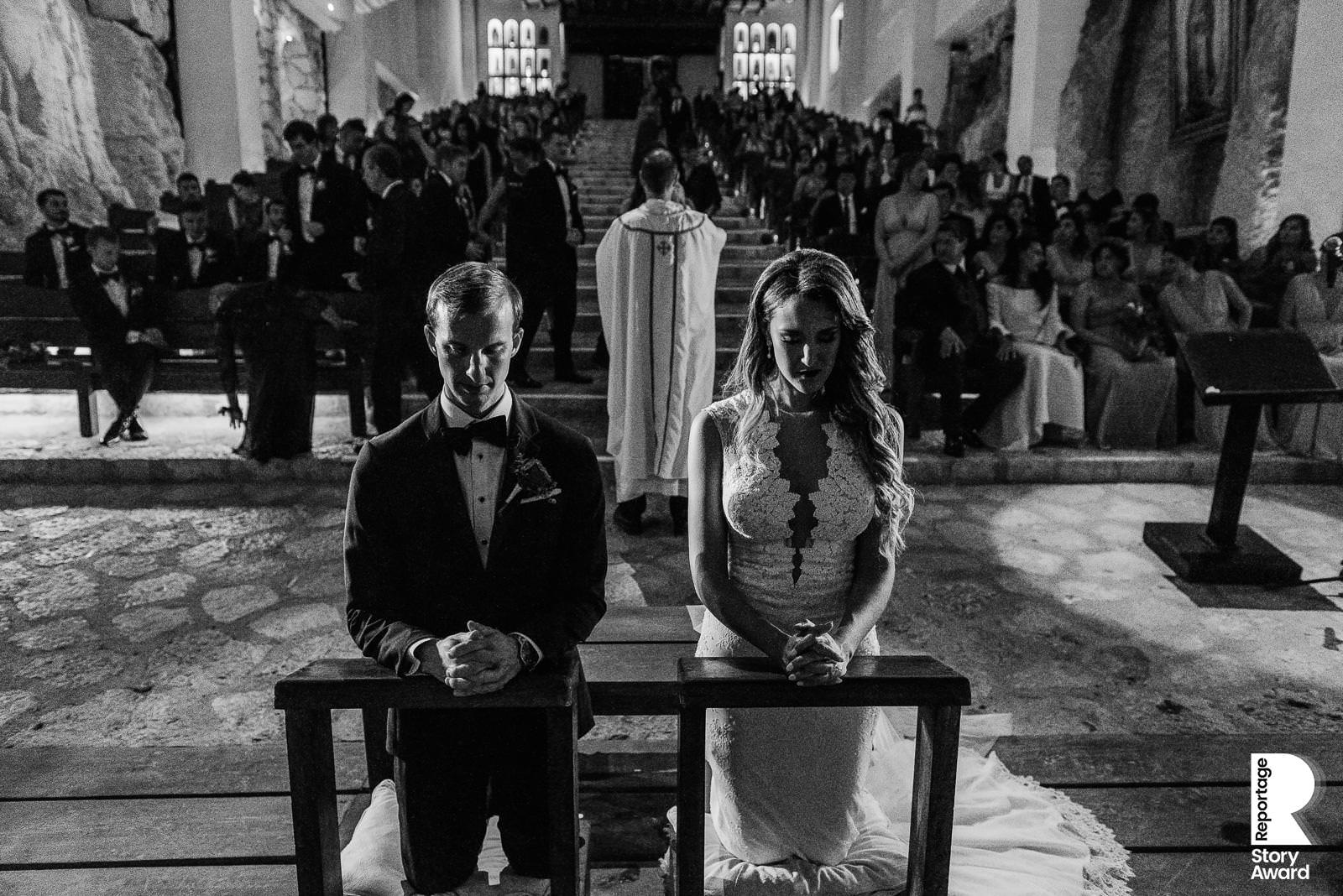 Mexico Destination Wedding Black and white photo of bride and groom praying on their knees at the Xcaret Chapel Altar