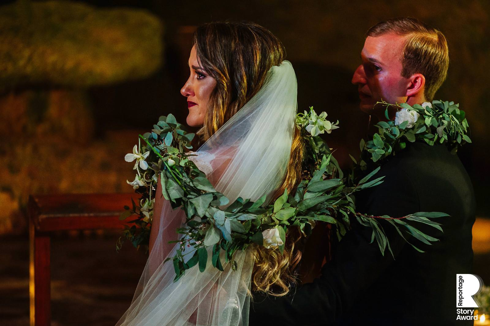 Close up of bride and groom with lazo of an emotional moment during Catholic wedding ceremony