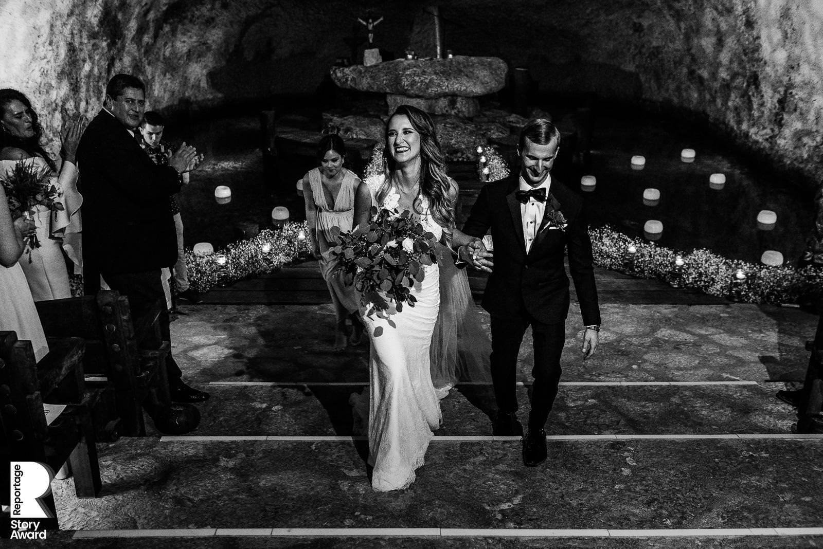 Bride and groom black and white image of them walking out the aisle holding hands at Xcaret Park Chapel