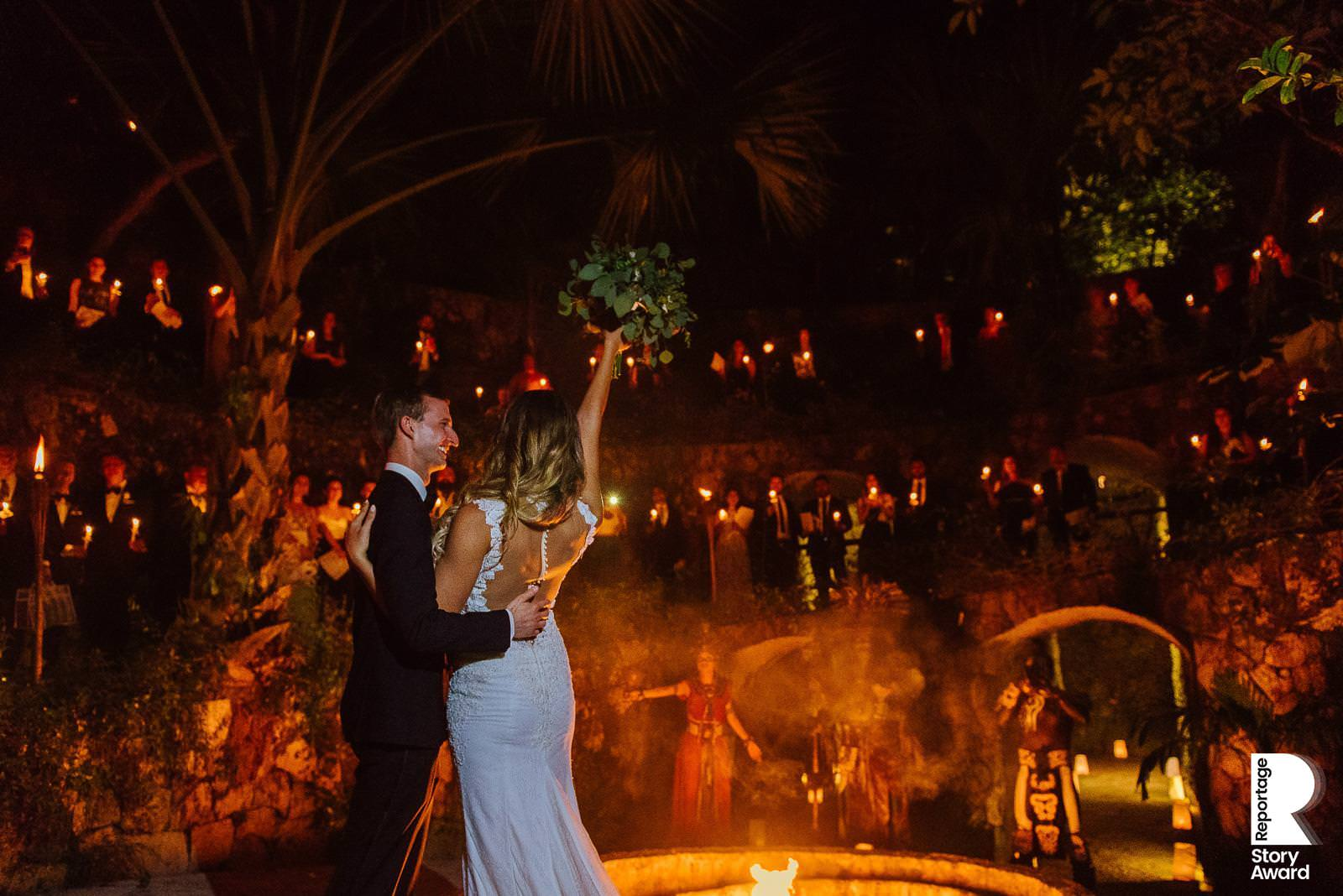 Mexico Destination Wedding Bride and groom meet their guests at El Caracol in Xcaret Park with fire, torches and mayan warriors