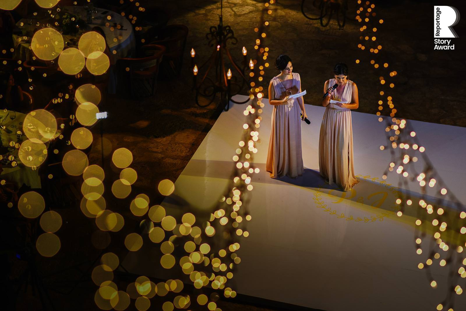 Wedding speech by maid of honor and bridesmaid at La Isla framed by string lights