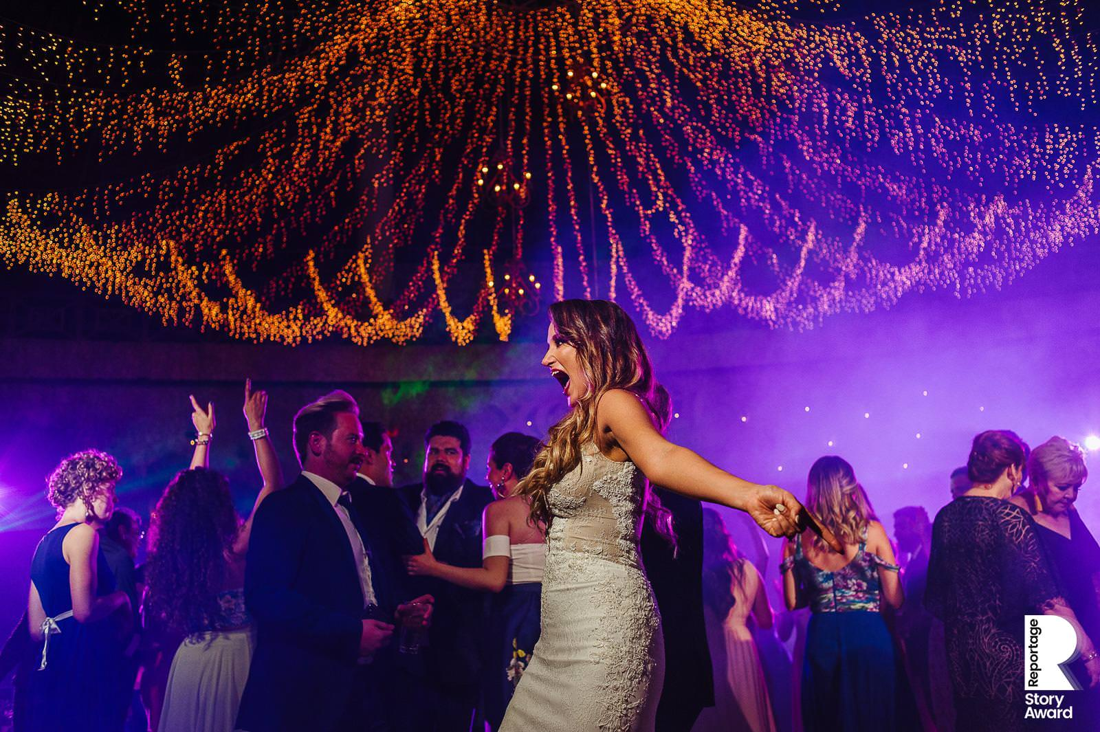 Bride walking on the dance floor with beautiful string lights and purple light