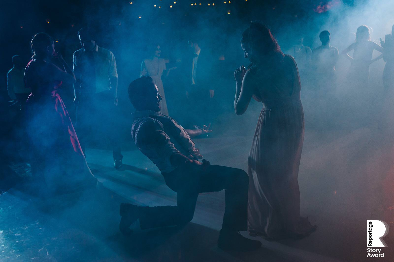 Guests dancing on the dance floor with dreamy blue light at Xcaret wedding reception