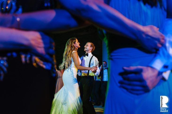 Bride and groom dancing framed with guests arms with purple and blue led lights