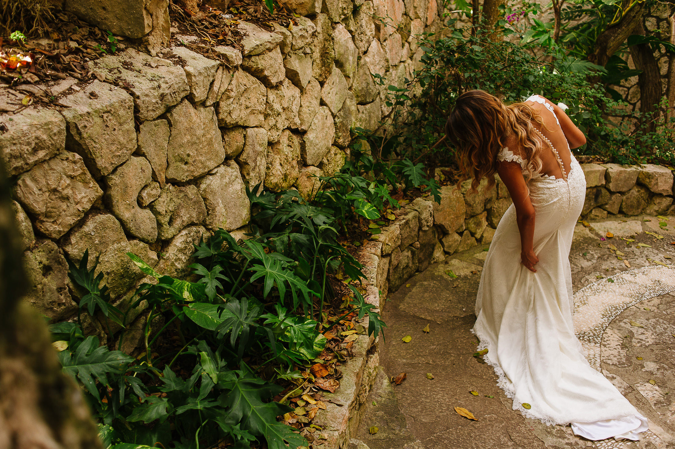 Birde holding up her train beside a wall of rocks and plants wedding gown by Ines Di Santo