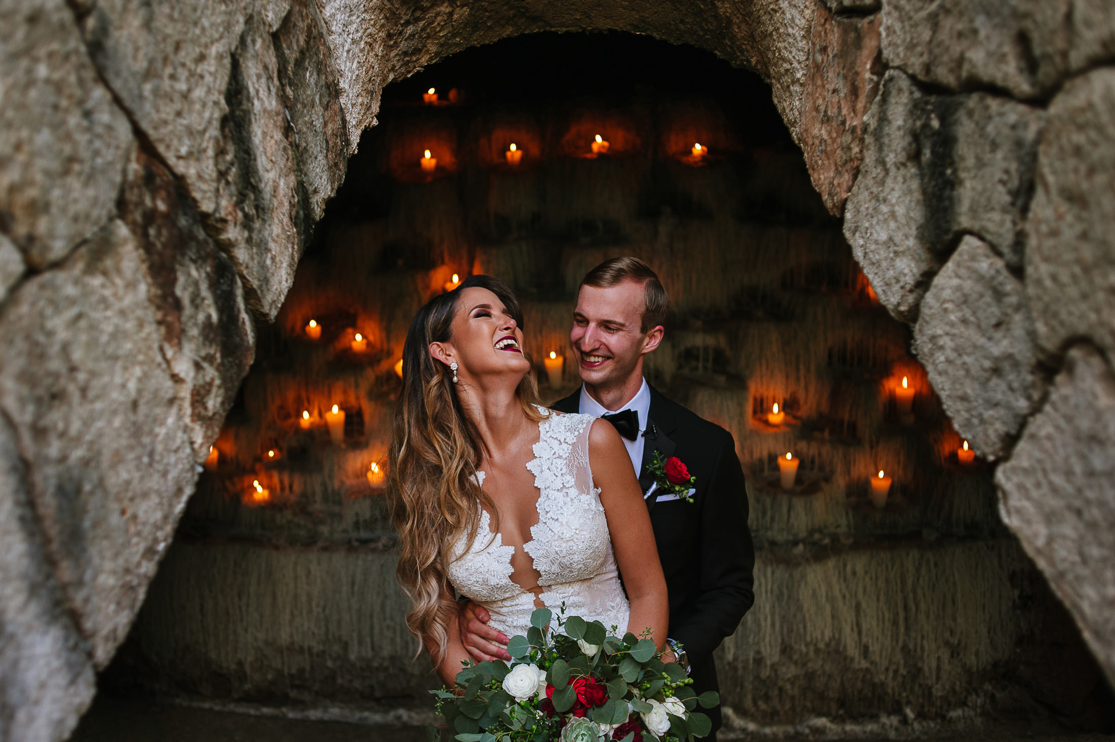 Bride and groom at Xcaret Park in front of the candles by Capilla de los Suspiros portrait
