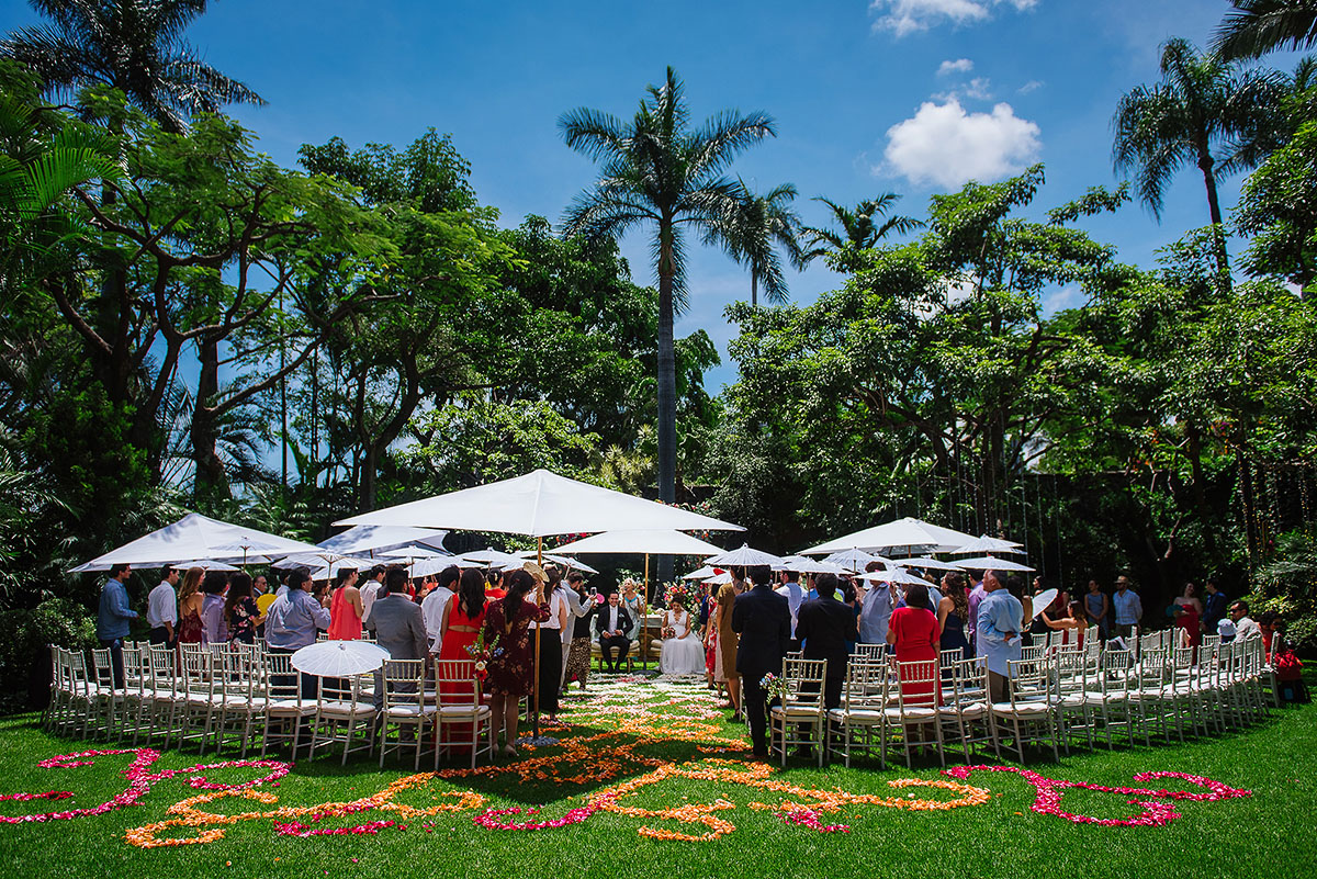 Gorgeous garden ceremony with white umbrellas and colorful decor