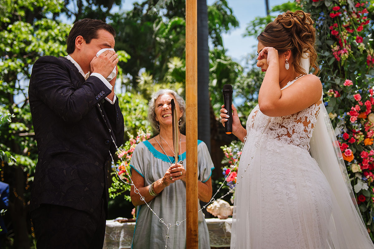 Bride and groom wipe out tears of joy during ceremony