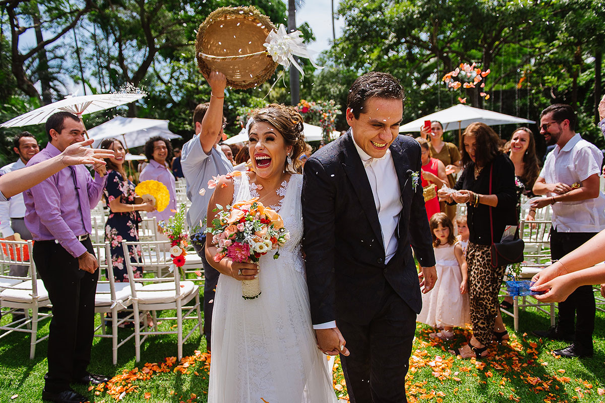 Bride and groom walk out the aisle together with rose pedals toss at them