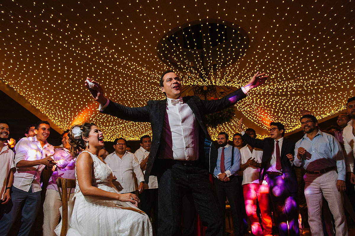 Garther toss bride and groom on dance floor and gorgeous string lights celing