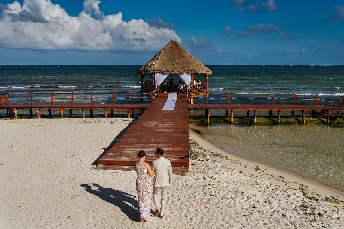 Walking down the aisle together for their dock wedding ceremony in Cancun