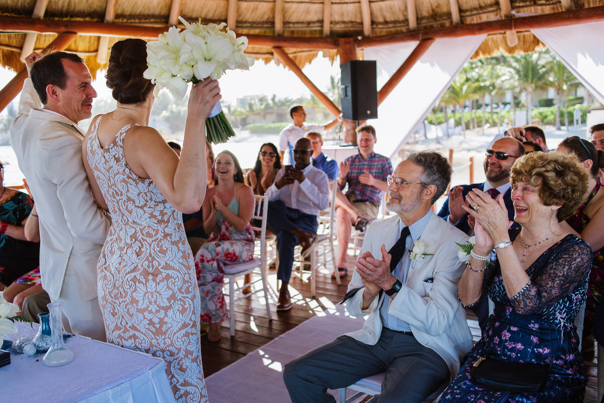 Bride and groom holding hands up after ceremony and family's reaction