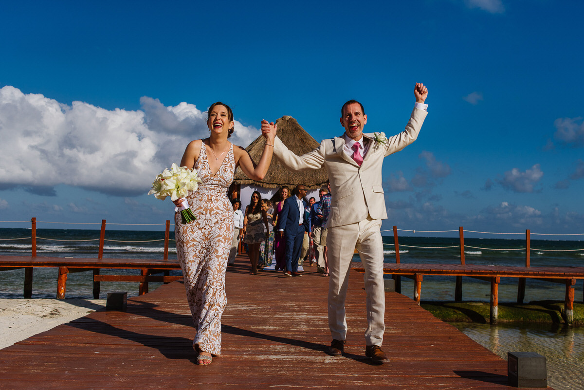 bride and groom after ceremony walking on pier super excited