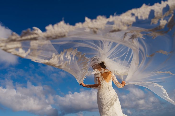 Bride playing with veil and wind in Playa del Secreto