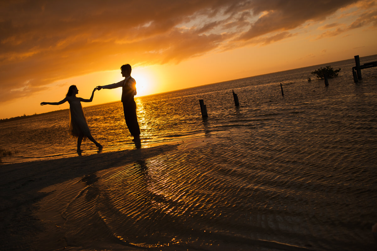 Bride and groom dancing in front of a beautiful sunset in Cancun