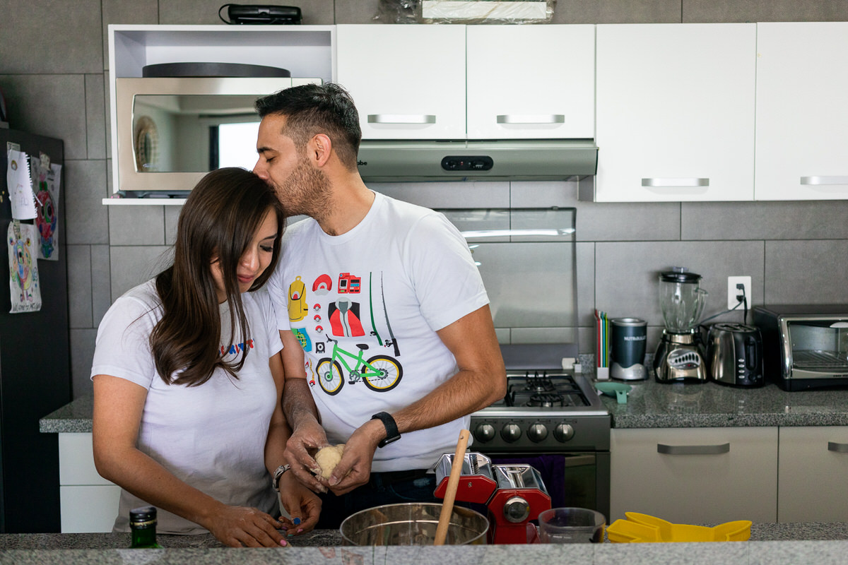 Couple save the date in Mexico City cooking pasta in the kitchen with geek t-shirts
