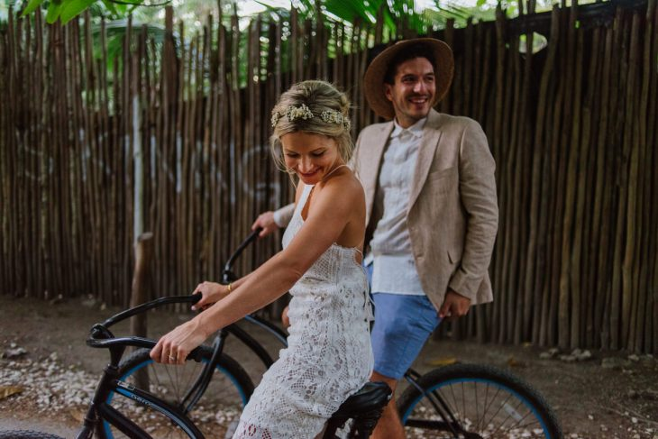 Bride and groom riding a bike in Tulum Mexico
