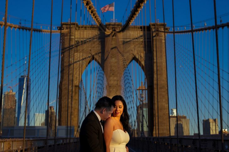 Groom kissing bride on the shoulder by the Brooklyn Bridge portrait