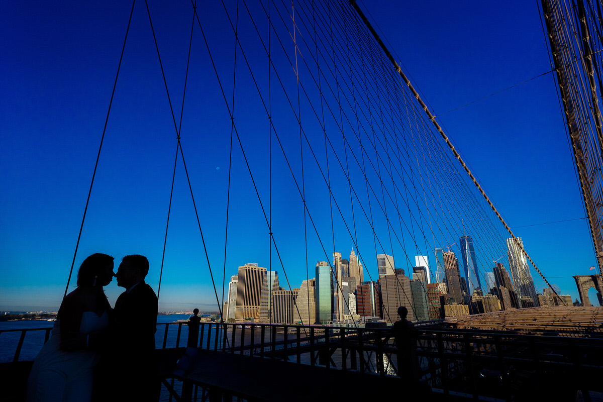 Silohuetted couple on the Brooklyn Bridge with Manhattan skyline in the back