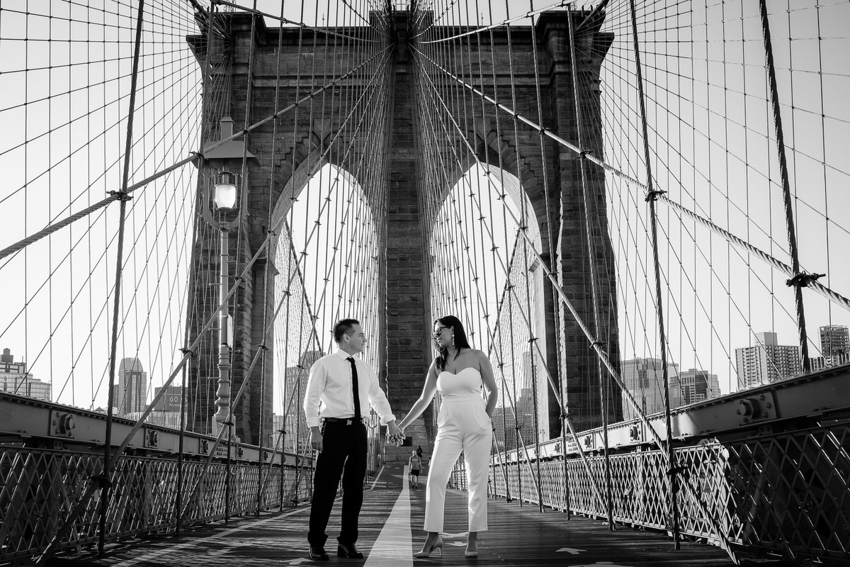 Black and white portrait in Brooklyn Bridge of couple celebrating their Anniversary